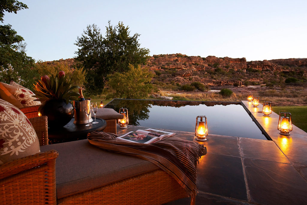 Couch with magazine, candles and champagne overlooking a pool and safari view at dawn